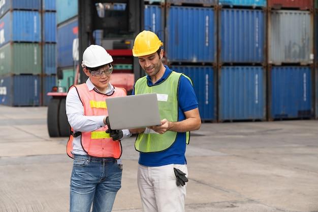 Ingenieur mit laptop, der die position beim laden von containern beim frachtcontainerversand überprüft