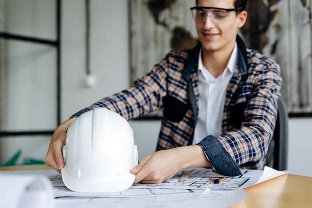 Ingenieur mit schutzhelm in seinen händen, die im büro arbeiten