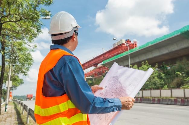 Ingenieur oder architekt tragen den weißen sturzhelm, der bauplan liest oder liest