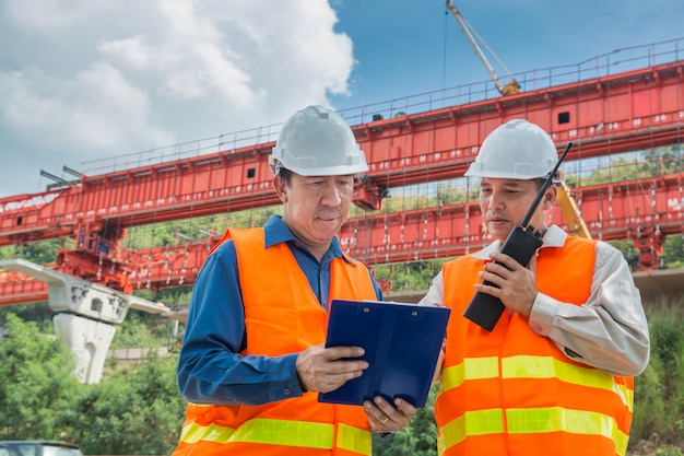 Ingenieur oder architekt wenden sich über funkkommunikation an, um das autobahn- oder autobahnprojekt zu überwachen oder zu verwalten