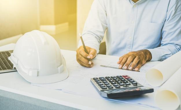 Ingenieur oder architekten, die planungsprojekt auf schreibtisch bearbeiten.