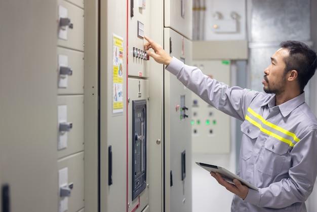 Ingenieur oder techniker mit tablet zur überwachung von prozess-, geschäfts- und industriekonzepten in schaltanlagen von öl- und gasplattformen oder anlagenindustrie.