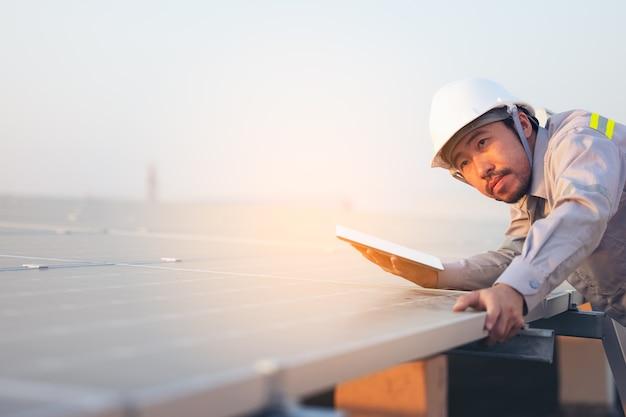 Ingenieur solar photovoltaik-module station überprüft mit tablet-computer. energietechnologiekonzept