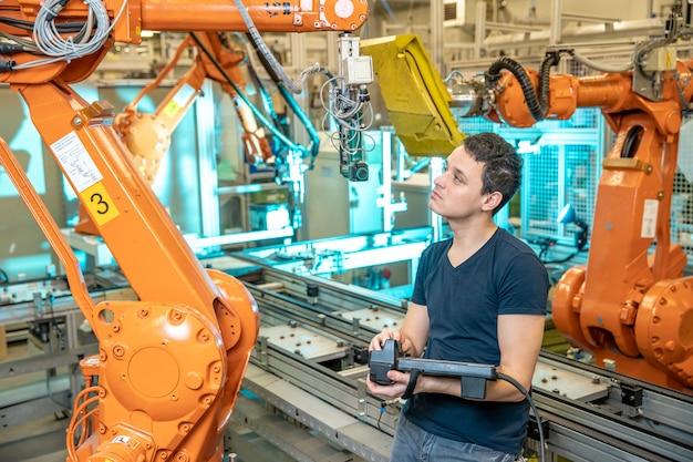 Ingenieur steuert mit der fernbedienung des industrieroboters im werk. automatisches schweißen und kleben mit automatisierungs- und roboterarmen