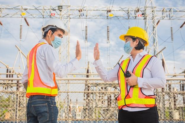 Ingenieur teamwork schütteln die hand keine berührung und tragen eine medizinische maske zum schutz des coronavirus covid19