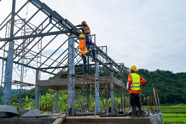Ingenieur techniker beobachtet team von arbeitern auf hochstahlplattform, ingenieur techniker sucht und analysiert ein unvollendetes bauprojekt.