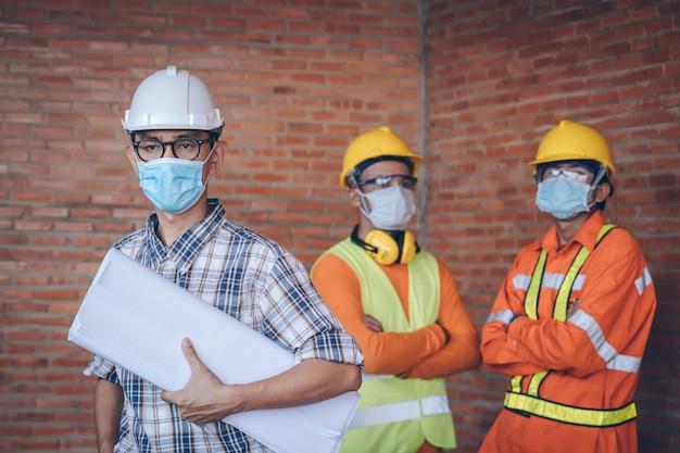 Ingenieur tragen schutzmasken für die coronavirus-krankheit 2019 (covid-19) auf der baustelle, health and construction concept.