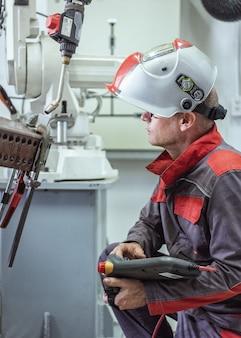 Ingenieur überprüfen und steuern die automatische waffenmaschine der schweißensrobotik in der intelligenten industriellen fabrikautomobilindustrie