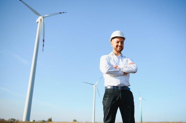 Ingenieur überprüft die energieproduktion einer windkraftanlage. arbeiter im windmühlenpark im helm.