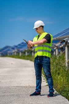Ingenieur überprüft installierte sonnenkollektoren im solarkraftwerk.