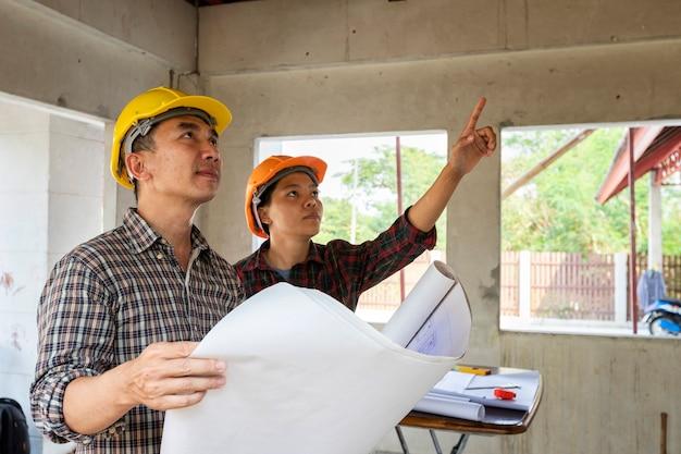 Ingenieur und architekt, die mit vorarbeiter im hochbaustandort sich besprechen