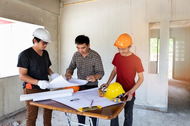 Ingenieur und architekt, die mit vorarbeiter im hochbaustandort sich besprechen.