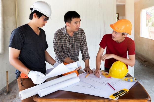 Ingenieur und architekt, die mit vorarbeiter in der baustelle sich besprechen.