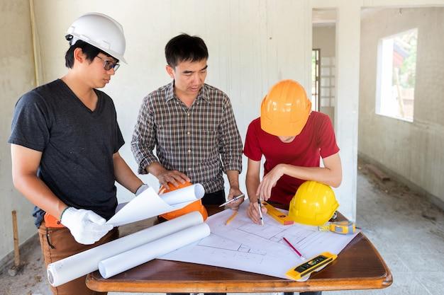 Ingenieur und architekt, die mit vorarbeiter in der baustelle sich besprechen