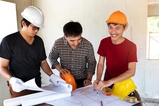 Ingenieur und architekt, die mit vorarbeiter über projekt in der baustelle besprechen.