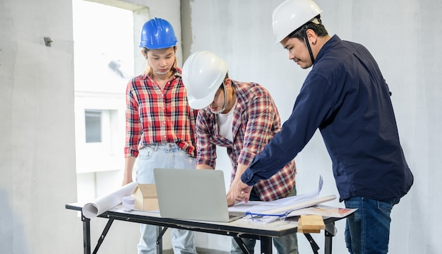 Ingenieur und architekten arbeiten und diskutieren auf der baustelle. eigentümerinspektion bei dorfprojekt und gutsgebäude.