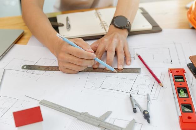 Ingenieur- und architektenkonzept, ingenieurarchitekten und innenarchitekt, die mit bauplänen arbeiten