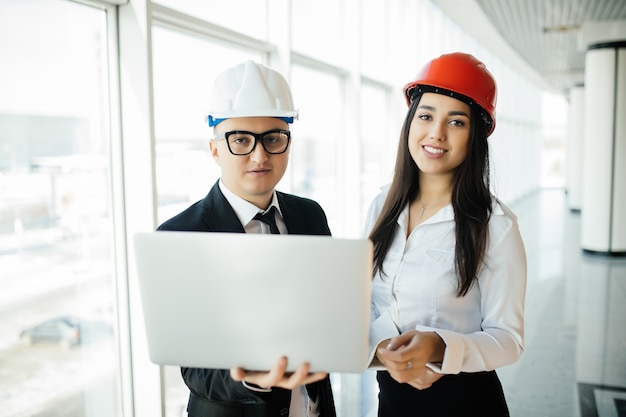 Ingenieur- und architekturkonzept. ingenieure, die auf einer baustelle arbeiten, die laptop hält, architektenmann, der mit inspektion der ingenieurin am arbeitsplatz für architekturplan arbeitet