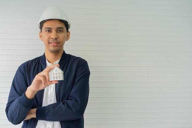 Ingenieur vorarbeiter, der das modell des hauses hält, das für immobilienprojektkonzept steht