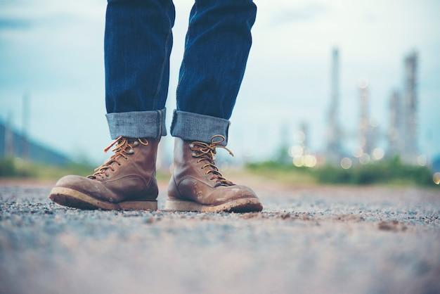 Ingenieur wear jeans und braune stiefel für arbeitnehmersicherheit auf hintergrund der raffinerie