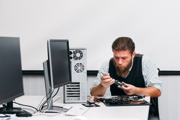 Ingenieur zerlegt dvd-laufwerk teil der cpu. cd-rom-renovierung in der werkstatt. elektronisches renovierungs-, geschäfts-, technologiekonzept
