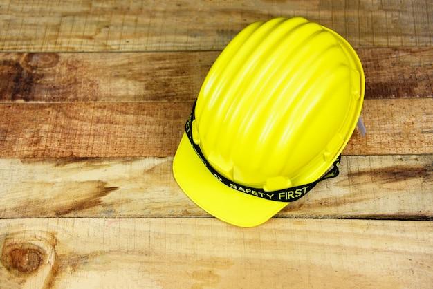 Ingenieurarbeitskraftsturzhelm auf hölzernem konzeptgelb des hintergrundes der sicherheit erstem hartem sicherheitsabnutzungs-sturzhelmhut