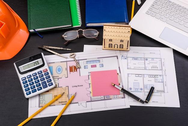 Ingenieurarbeitsplatz mit laptop und hausplan