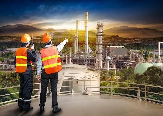 Ingenieurbefragung der ölraffinerie am lagertank im sonnenuntergangshintergrund