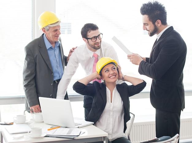 Ingenieurbüro mit den älteren und jungen architekten, die an neuem projekt arbeiten