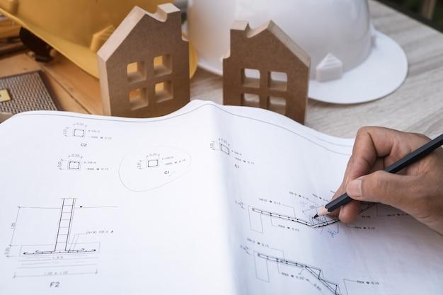 Ingenieure, architekten, handzeichnung oder überprüfung der bauplankonstruktion auf einem blaupausendokument für den bau eines hauses oder eines eigentumswohnungsprojekts mit hut, holzhausmodell oder ausrüstung auf dem schreibtisch