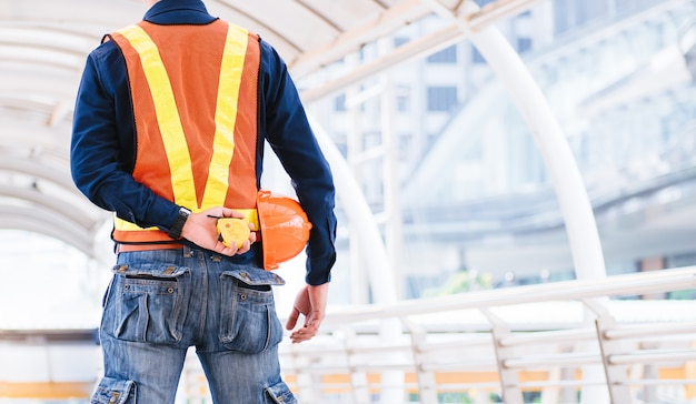Ingenieure bereiten sich mit orange helm und maßband auf den job vor.