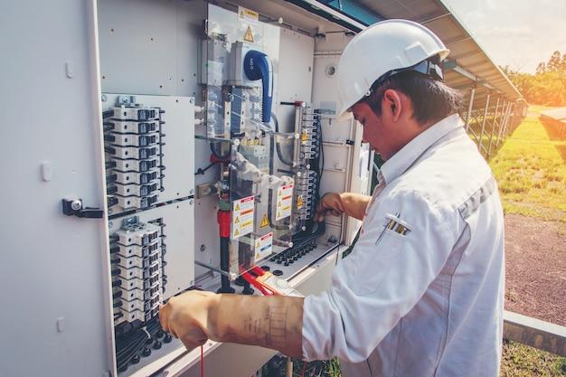Ingenieure, die an überwachungs- und wartungsgeräten arbeiten: checken des wechselrichterstatus