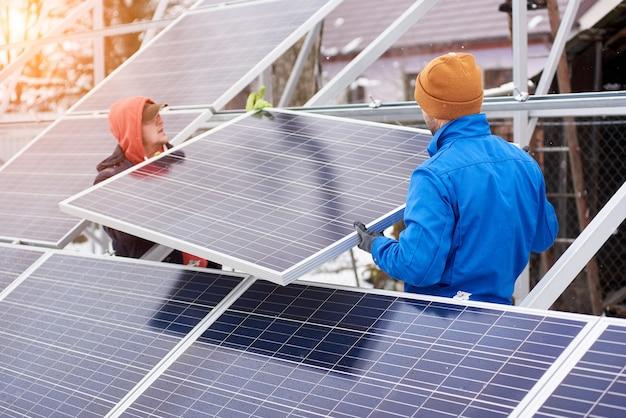 Ingenieure, die im winter sonnenkollektoren installieren