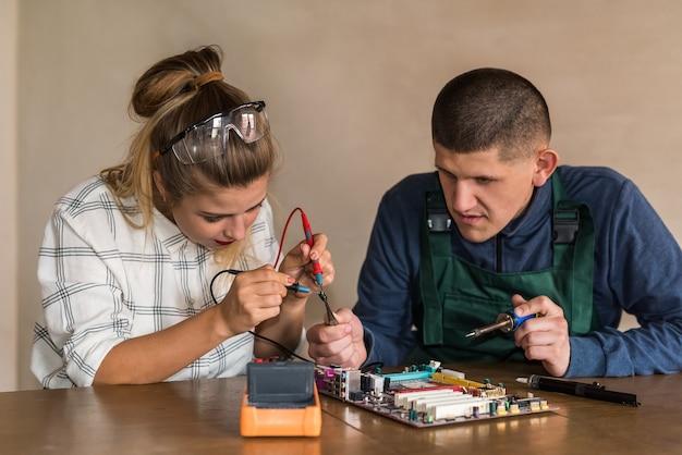 Ingenieure, die mit motherboard arbeiten, reparieren einige details