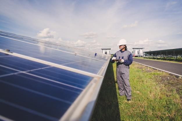 Ingenieure, die sonnenkollektoren bei der stromerzeugung des sonnenkraftwerks reparieren; techniker in industrieuniform auf ebene der berufsbeschreibung bei industrie