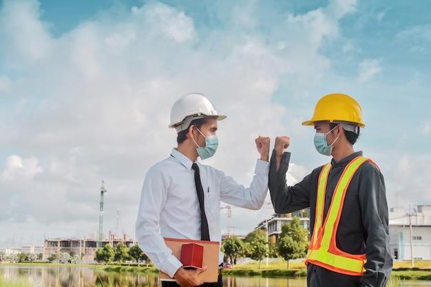 Ingenieure grüßen sich gegenseitig, indem sie die ellbogen berühren. zwei geschäftsleute geben der baustelle im freien keine berührung