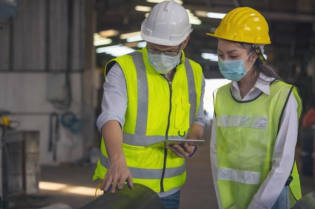 Ingenieure in der stahlfabrik arbeiten an digitalem tablet. qualitätskontrollmanagement.