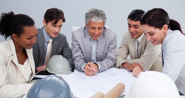 Ingenieure in einer sitzung, die pläne studiert