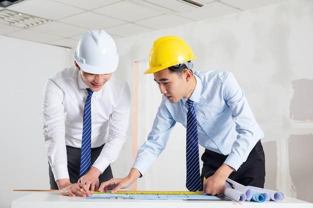 Ingenieure in helmen, die zur fabrik stehen