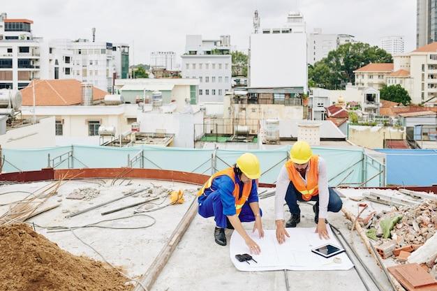 Ingenieure in schutzhelmen diskutieren blaupausen, wenn sie an im bau befindlichen gebäuden arbeiten
