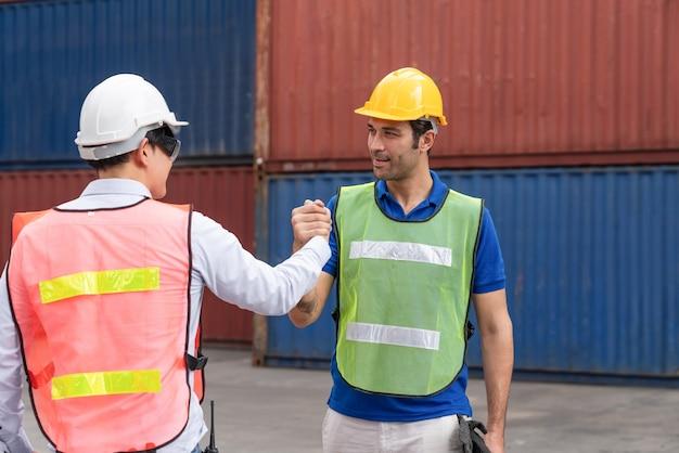 Ingenieure schließen sich den händen an, um erfolgreich beim laden von containern beim frachtcontainerversand zu arbeiten