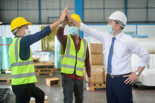 Ingenieure tragen eine gesichtsmaske, die in einer modernen fabrik glücklich ist, ein erfolgreiches industrielles und teamwork-konzept