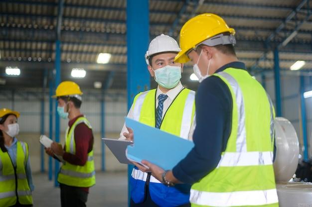 Ingenieure tragen schutzmasken, die im lager arbeiten