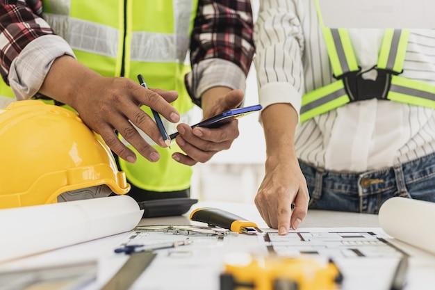 Ingenieure und architekten zeigen auf die für den bauherrn entworfenen hauspläne, besprechungsatmosphäre, sie treffen sich zusammen, um den bau zu planen und zu reparieren. design- und einrichtungsideen.