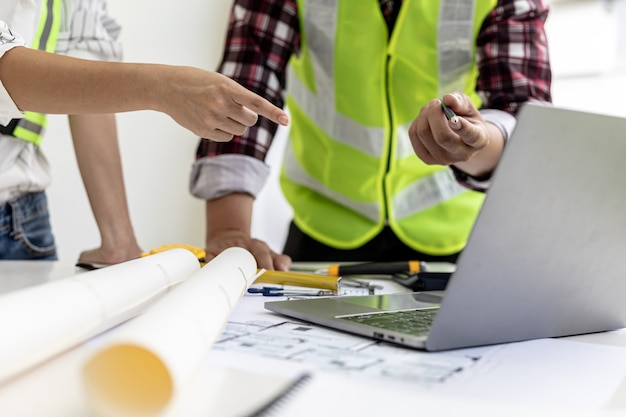 Ingenieure und architekten zeigen auf laptop-bildschirme und sehen sich pläne an, um einige änderungen vorzunehmen, sie treffen sich, um bau und reparaturen zu planen. design- und einrichtungsideen.