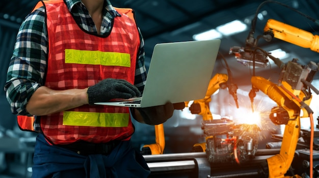 Ingenieure verwenden fortschrittliche robotersoftware, um den roboterarm der industrie in der fabrik zu steuern