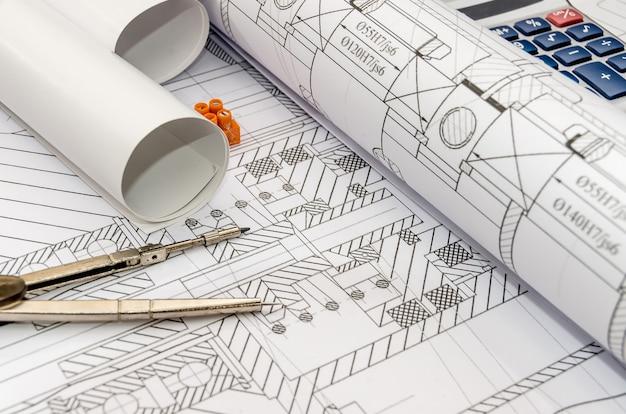 Ingenieure zeichnen mit kompass, taschenrechner und rollen