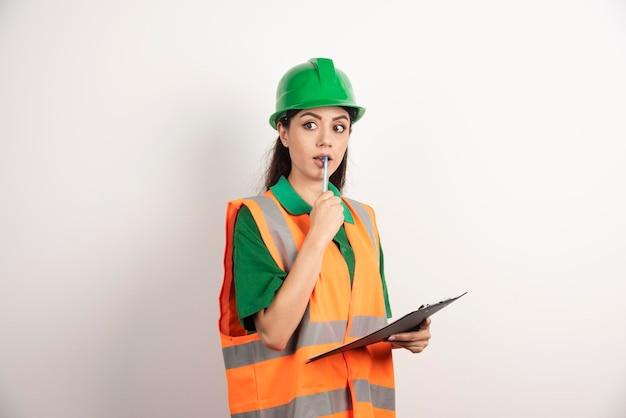 Ingenieurfrau, die geschäftspapier und bleistift hält. foto in hoher qualität