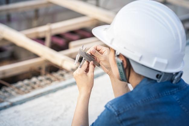 Ingenieurfrau, die messschieber für das messen eines objekts auf der baustelle hält. der arbeiter stellt den messschieber ein.
