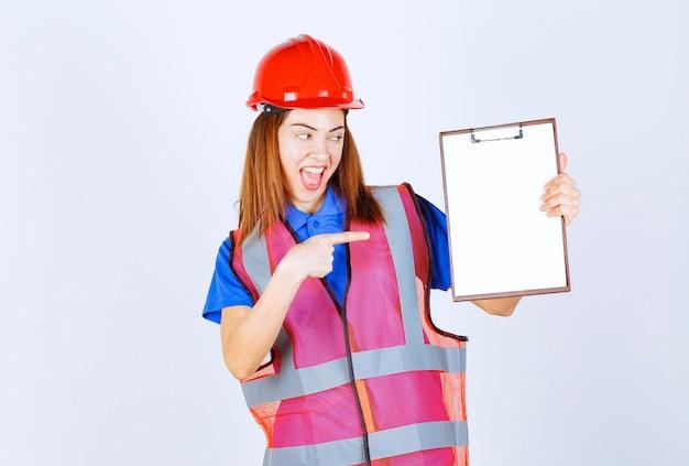 Ingenieurfrau in uniform, die eine leere berichtsdatei hält.